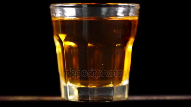 Pohár az asztalon, a sötét háttér előtt a stúdióban spinning friss whisky