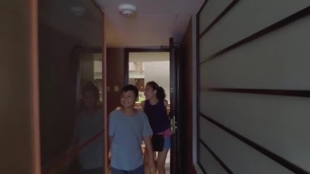 Singapur. 11. prosince 2017: Šťastná rodina přijíždí v pokoji Luxusní pětihvězdičkový hotel při jejich kufrem a ležel na posteli společně. Zastřelen v Marina Mandarin Hotel Singapore