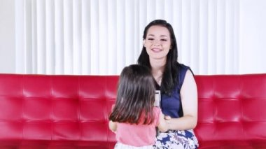 Happy young mother getting a gift box from her daughter while sitting on a red sofa in the living room at home