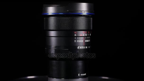 Riprese video di un obiettivo fotografico sopra priorità bassa scura in studio