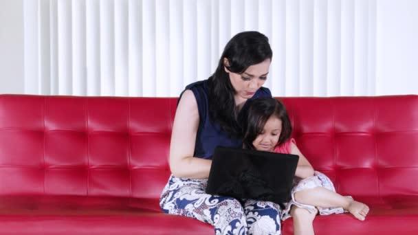 Mladá matka a její dcera, zatímco sedí na červenou pohovku v obývacím pokoji doma společně pomocí přenosného počítače