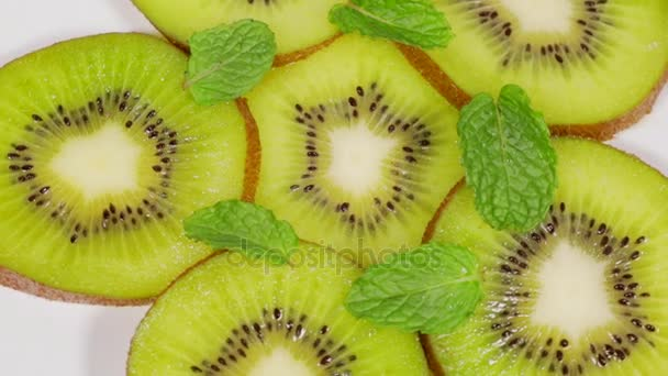 Top view of slices of juicy kiwi fruit spinning on the table in the studio