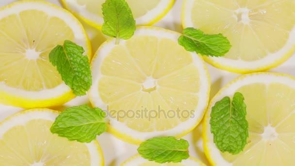Video záběry plátky citronu ovoce a máta listy předení na stůl