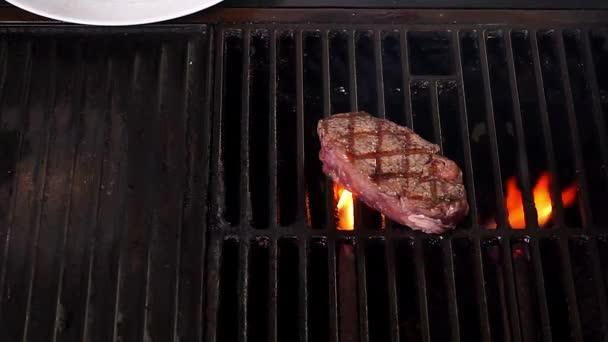 Zblízka grilování hovězí steak na hořící gril v restauraci