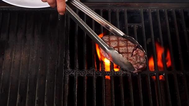 Pohled shora na hovězí steak na grilu s plamenem v restauraci na grilu