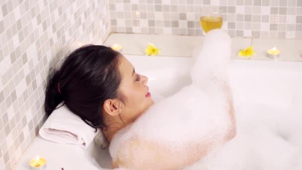schöne Frau entspannt sich in der Badewanne und trinkt ein Glas Wein mit Schaum und Frangipani-Blumen