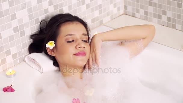 Wellness-Behandlungskonzept. hübsche junge Frau entspannt sich in der Badewanne mit Frangipani-Blumen und Schaum