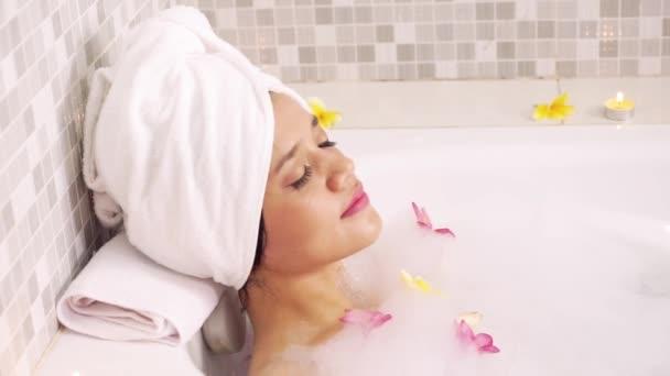 Hezká žena užívat si koupání ve vaně s pěnou a keře květy při nošení ručník na hlavě