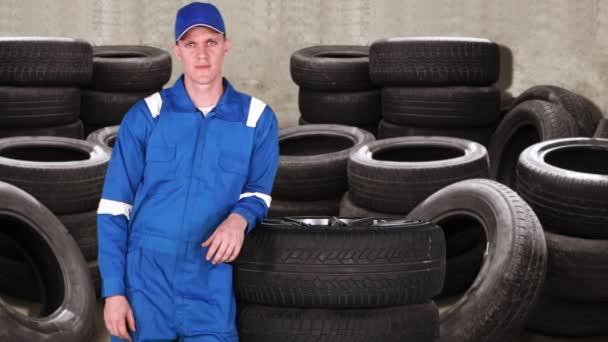 Kavkazská automechanik ukazuje palec s hromady pneumatik na pozadí