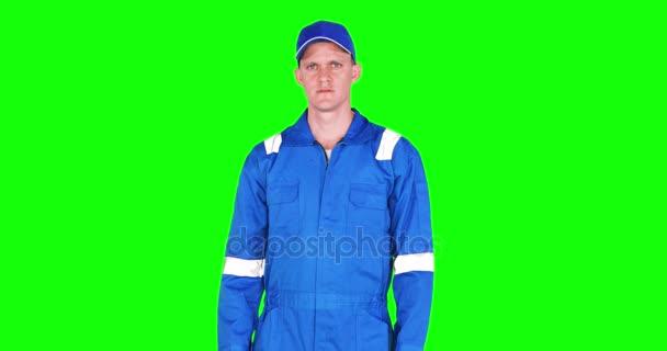 männlicher kaukasischer Mechaniker zeigt im Studio Daumen nach oben, während er blaue Uniform trägt, aufgenommen in 4k Auflösung