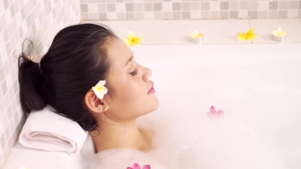 Spa concept. Beautiful young woman enjoying spa treatment in bathtub with foam and frangipani flowers