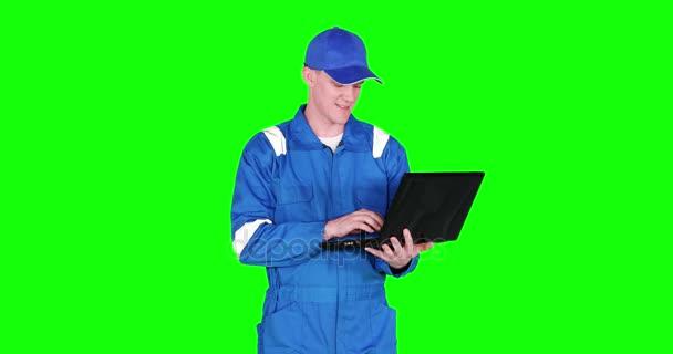 männliche kaukasische Automechaniker, die mit einem Laptop arbeiten, während sie blaue Uniform tragen und im Studio stehen, aufgenommen in 4k-Auflösung mit grünem Hintergrund