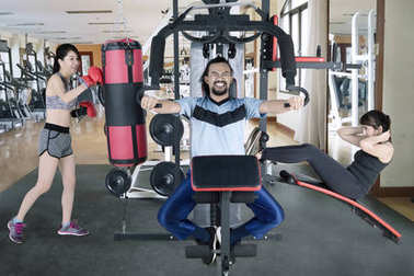Three people doing a workout with gym equipment