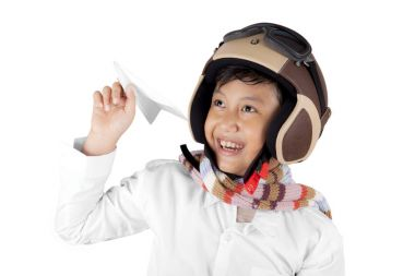 Smiling Asian boy wearing vintage flight helmet holding a plane paper isolated over white background stock vector