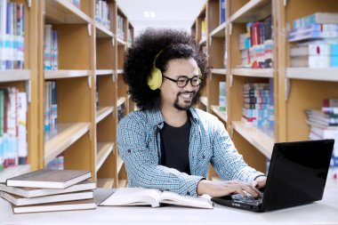 Male student hearing music in the library