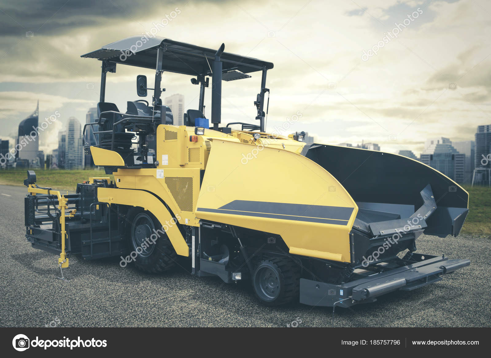 asphalt spreader or asphalt pavers machine parking on road construction site photo by realinemedia