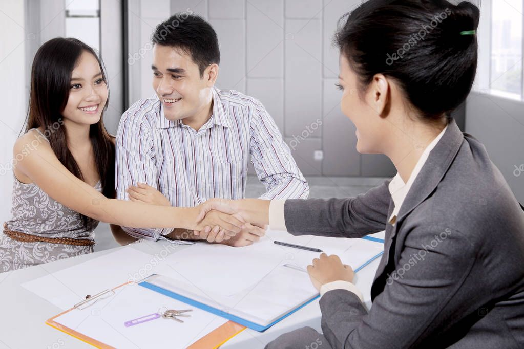 Young couple with a real estate agent come to an agreement