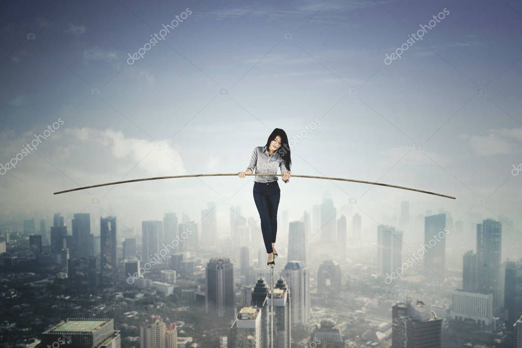 Beautiful businesswoman balancing on a rope