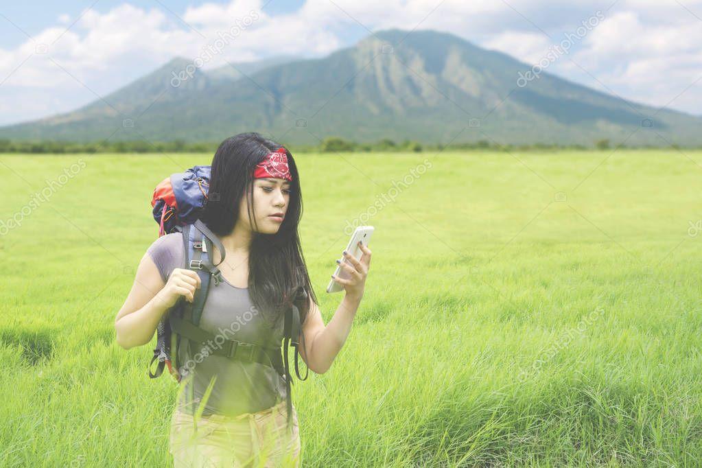 Beautiful backpacker checking navigation on mountain