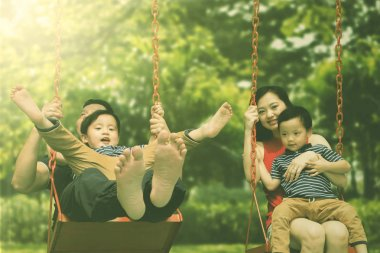 Image of happy parents playing on the swing with their sons. Shot in the park stock vector