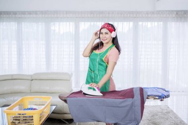 Beautiful Asian woman posing while ironing