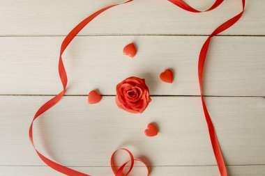 Top view of ribbon surrounding a rose and candies