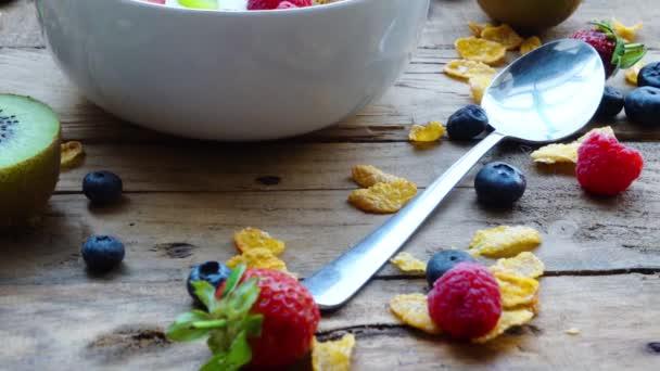 Detailní záběr misky zdravé snídaně s cereáliemi a čerstvými bobulemi na dřevěném stole. Snímek v rozlišení 4k