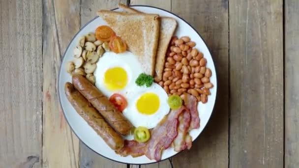 Anglický koncept snídaně. Detailní záběr dvou smažených vajec podávaných s klobásou, slaninou, fazolemi a tousty na talíři