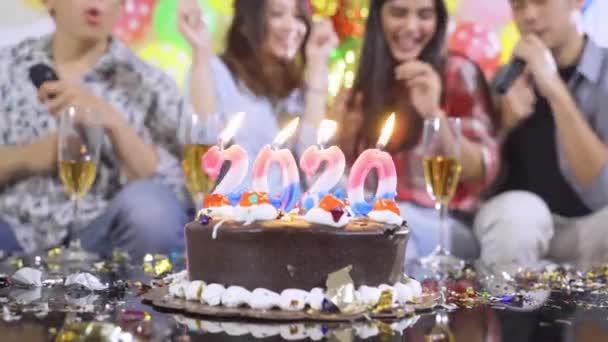 Narozeninový dort s 2020 Nový rok svíčky s rozmazané šťastní lidé pozadí slaví narozeninovou oslavu s slavnostní výzdobou. Snímek v rozlišení 4k