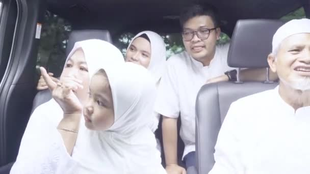Happy muslim family on a road trip in their car