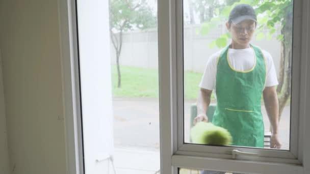 Haushälterin putzt Fenster mit Staubwedel