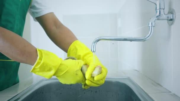 Hausmeister wäscht einen schmutzigen Schwamm in der Spüle
