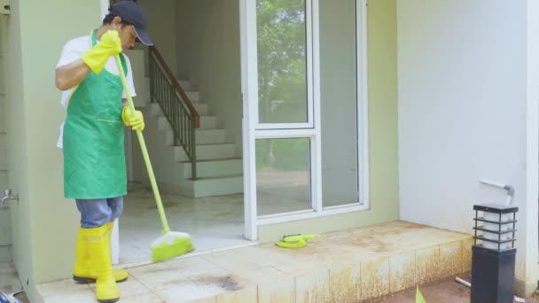 Muž pracovník zametání prašné podlahy terasy domu
