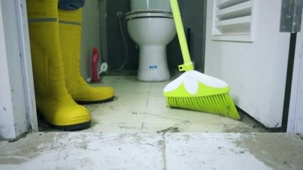 Pracovník nohy zametání podlahy v nepoužité koupelně