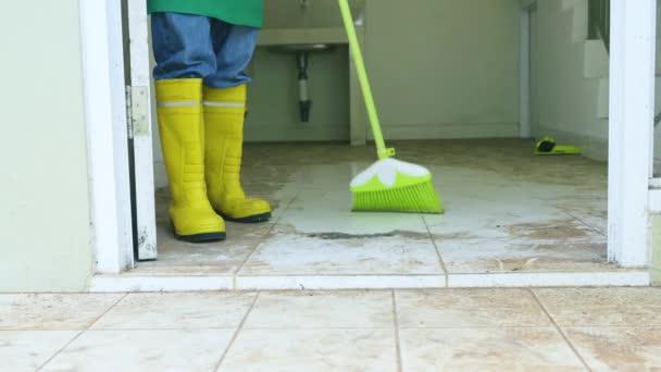 Dělnické nohy zametají podlahy v nepoužívaném domě