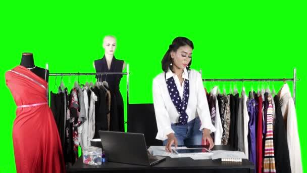 Módní návrhářka kontroluje své vlastní oblečení