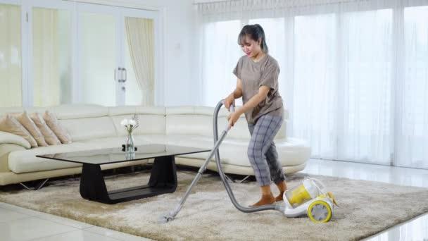 Schöne Hausfrau putzt Teppich mit Staubsauger, während sie zu Hause im Wohnzimmer tanzt. Aufgenommen in 4k-Auflösung