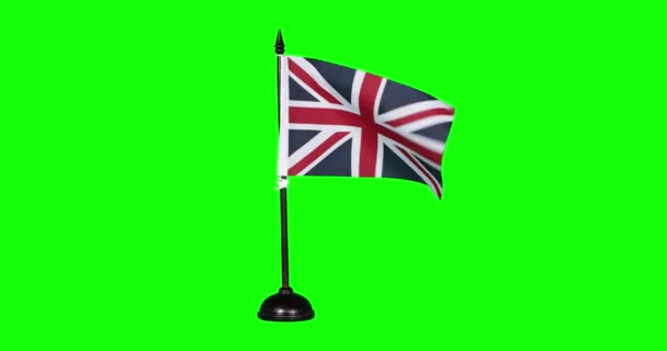miniature flag of United Kingdom fluttering on a flagpole, green background