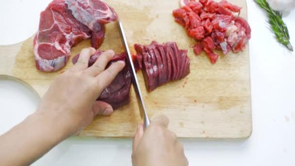 Detailní záběr rukou řezání červeného masa nožem