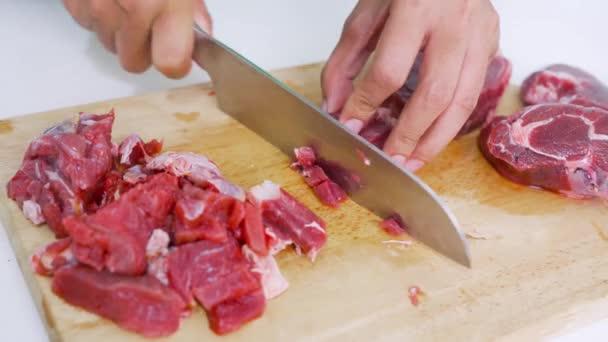 Detailní ruční řezání červeného masa nožem na olejovité řezací desce, zatímco koření v okolí kuchyně