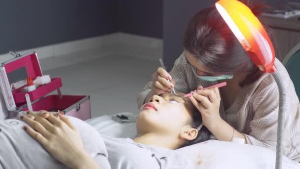 Junge Frau unterzieht sich einer Wimpernverlängerung im Schönheitssalon, Nahaufnahme