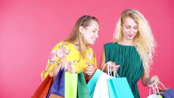 Két fiatal nő bevásárlószatyrot hord a stúdióban.