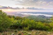Západ slunce na šířku panorama, hills v zlaté hodiny, malé vesnice v údolí, krásné barvy a mraky