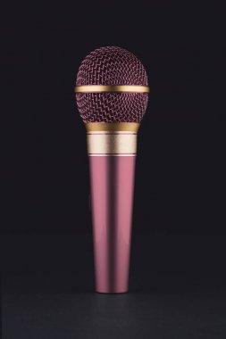 A pink wireless microphone on a black background