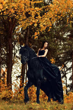 a girl in a black dress and a black tiara on a Frisian horse ride on a magical fairytale forest