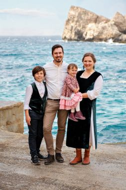 portrait of cute smiling family in retro rural old-fashioned outfits against the sea ocean background with rocks
