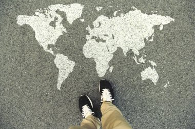 World map on an asphalt road. Top view of the legs and shoes. POV stock vector