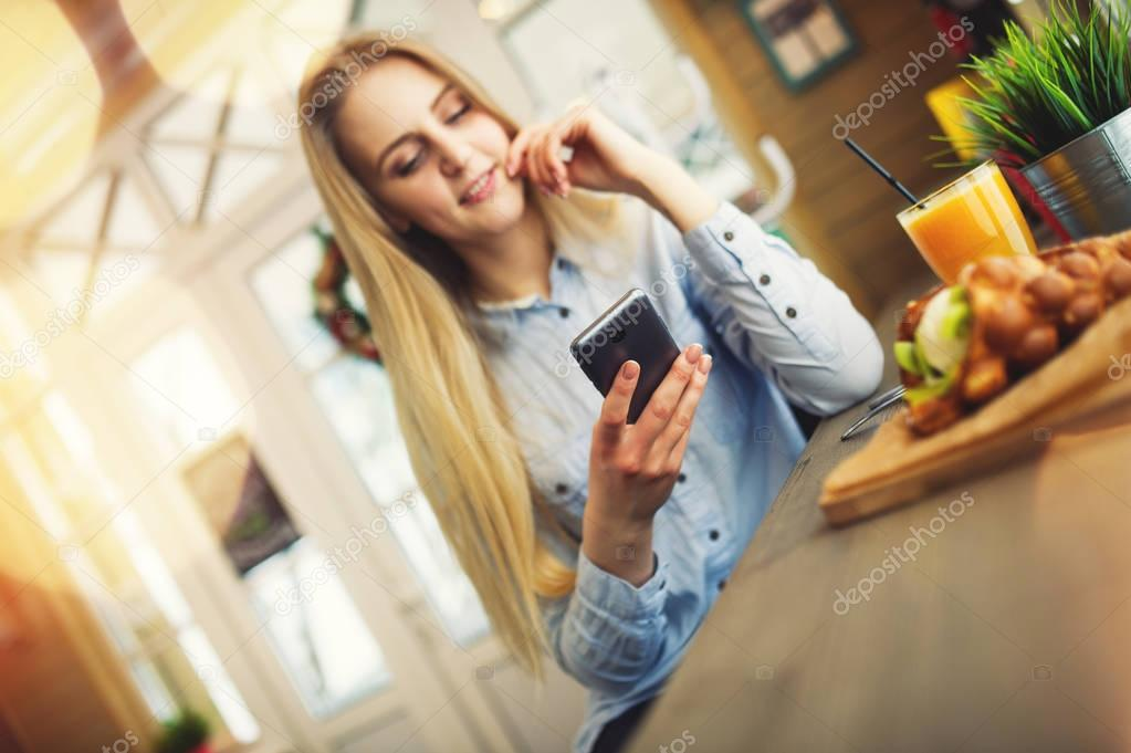 Beautiful woman checks news in the social networks on your phone in a cozy cafe in the style of Provence