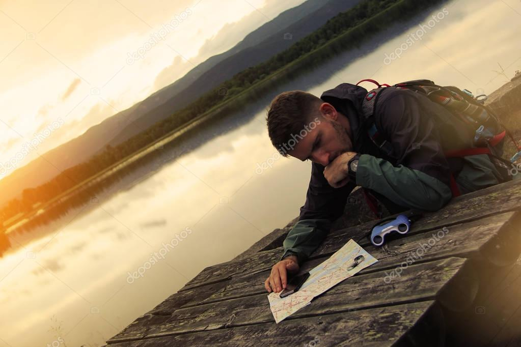 Thoughtful traveler, sitting at  wooden table near a lake and looking at a map