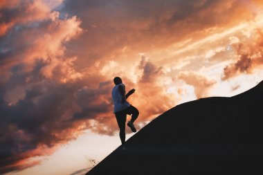 Athlete runs around the hills. Strong athlete runs through the mountains at sunset